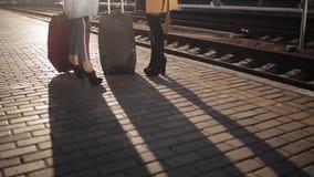 Dwa kobiety opowiada na platformie stacja kolejowa zmierzchu światło i cienie ludzie na bruku, zbiory