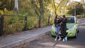 Dwa kobiety opowiada stać przy kapiszonem parkujący zielony samochód zbiory