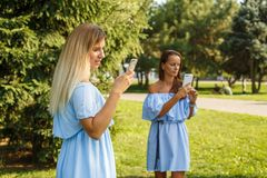 Dwa kobiety patrzeje w ich smartphones w lato zieleni parku fotografia stock
