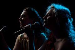 Dwa kobiety śpiewa w mikrofonie Obrazy Royalty Free