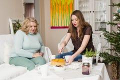 Dwa kobiety pije herbaty blisko choinki Matka z córką Zdjęcie Royalty Free
