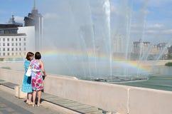 Dwa kobiety podziwiają tęczę w fontannie w jeziornym dnie Bo Fotografia Royalty Free