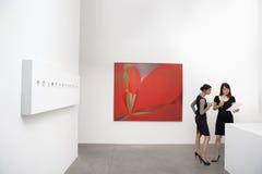 Dwa kobiety pozyci obok ściennych obrazów Obrazy Stock