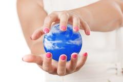 Dwa kobiety ręki Ochrania niebieskie niebo sferę Obrazy Royalty Free
