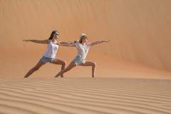 Dwa kobiety robi joga w pustyni Zdjęcia Stock
