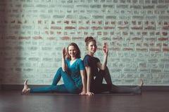 Dwa kobiety robi partnera joga w joga pracowniany naprzeciw ściany z cegieł zdjęcie royalty free