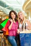 Dwa kobiety robi zakupy z torbami w centrum handlowym Obrazy Stock