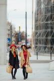 Dwa kobiety ruchliwie odprowadzenie na ulicie, opowiada z each inny zdjęcia stock