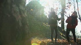 Dwa kobiety rzucają liście w powietrze strzelającego od zwolnionego tempa daleko wewnątrz zbiory