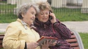 Dwa kobiety siedzą outdoors i dyskutują o naturze zbiory