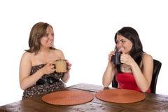 Dwa kobiety siedzi mieć kawę przy stołem Zdjęcia Royalty Free