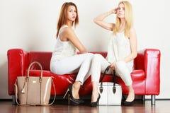 Dwa kobiety siedzi na kanapie przedstawia torby obraz royalty free