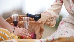 Dwa kobiety siedzi na koc i nalewa czerwone wino w szkłach - Tuscany zbiory