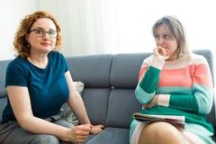 Dwa kobiety siedzi na popielatej kanapie i dyskutować obraz stock