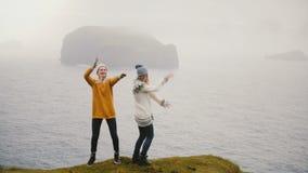 Dwa kobiety szczęśliwy taniec na brzeg morze w Iceland Rozochoceni turyści bada nowego kraju i ma zabawę zbiory