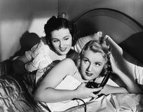 Dwa kobiety w łóżku z telefonem (Wszystkie persons przedstawiający no są długiego utrzymania i żadny nieruchomość istnieje Dostaw Obrazy Stock