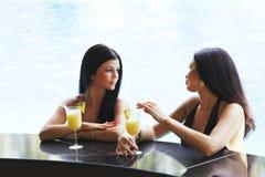 Dwa kobiety z koktajlami w pływackim basenie Zdjęcia Stock