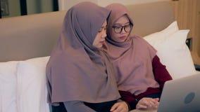 Dwa kobiety zegarka młody muzułmański wideo na laptopie w sypialni zbiory