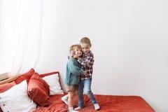 Dwa kochającego małego dziecka stoi na łóżku, przytuleniu i ono uśmiecha się, zdjęcie royalty free