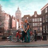 Dwa kochanków osoba w Amsterdam na tle barwiący dom w holendera stylu chwyta i stojaka rękach obraz stock