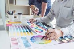 Dwa koleg?w kreatywnie projektant grafik komputerowych pracuje na koloru rysunku na grafiki pastylce i wyborze przy miejscem prac zdjęcia royalty free