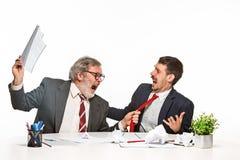 Dwa kolegi pracuje wpólnie przy biurem na białym tle obraz stock