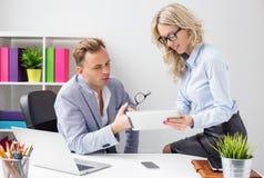 Dwa kolegi pracuje wpólnie w biurowym i patrzeje pastylka komputerze fotografia royalty free