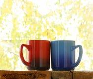 Dwa kolorowego kawowego kubka Zdjęcia Royalty Free
