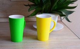 Dwa kolorowego kubka są na kuchennym stole z kwiatem Fotografia Stock
