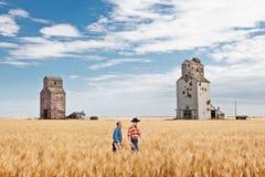 Dwa kowbojskiego rolnika chodzi w pszenicznym polu windami Obrazy Stock