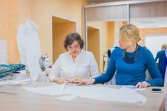 Dwa krawczyny dyskutuje wzór nowa suknia obraz stock