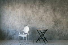Dwa krzesła przeciw szarej betonowej ścianie Pokój w loft stylu drewniane podłogi Światło dzienne Uwalnia przestrzeń dla teksta zdjęcie royalty free