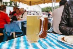 Dwa kubka z lekkiego i ciemnego piwa stojakiem na stole W tle, zamazujący ludzie Świętować tradycyjnego Obraz Royalty Free
