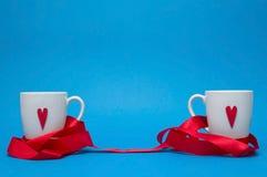Dwa kubka z sercami łączącymi z czerwonym faborkiem Obrazy Royalty Free