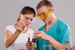 Dwa laboranckiego asystenta, dodają czerwonego ciecz kolba z zielonym cieczem z pomiarową pipetą zdjęcia royalty free