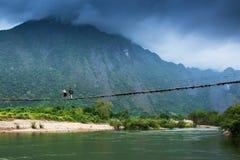 Dwa Laos dziewczyny chodzi przez zawieszenie most nad Nam Pieśniową rzeką, fantastycznym tłem, chmurnego i pasma górskiego obrazy stock