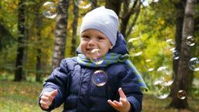 Dwa lat chłopiec bawić się w parku z mydlanymi bąblami zbiory wideo