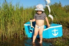 Dwa lat chłopiec na jeziorze z teleskopem i statkiem Fotografia Stock