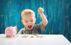 Dwa lat dziecka obsiadanie na kładzeniu i podłoga moneta w piggybank Zdjęcie Stock