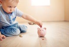 Dwa lat dziecka obsiadanie na kładzeniu i podłoga moneta w piggybank Fotografia Stock