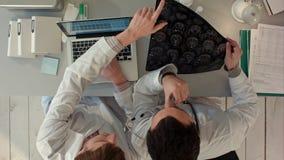 Dwa lekarka mężczyzna egzamininują obrazowanie rezonansem magnetycznym Odgórny widok zdjęcie stock