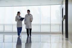Dwa lekarki chodzi i ono uśmiecha się w szpitalnej, pełnej długości, fotografia stock