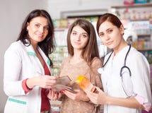 Dwa lekarki i jeden klient wśrodku apteki Obraz Stock