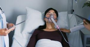 Dwa lekarki miewa skłonność żeński pacjent w łóżku szpitalnym 4k zbiory