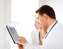 Dwa lekarki patrzeje promieniowanie rentgenowskie na pastylka komputerze osobistym Obrazy Stock