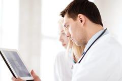 Dwa lekarki patrzeje promieniowanie rentgenowskie na pastylka komputerze osobistym Fotografia Royalty Free