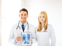 Dwa lekarki pokazuje promieniowanie rentgenowskie na pastylka komputerze osobistym Zdjęcia Royalty Free