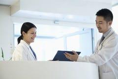 Dwa lekarki stoi kontuarem i patrzeje w dół przy dokumentem w szpitalu zdjęcia royalty free