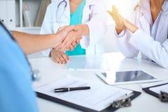 Dwa lekarki trząść ręki each inny przy spotkaniem Praca zespołowa i zgoda w medycynie obraz royalty free