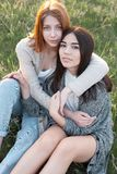 Dwa ślicznej dziewczyny siedzi na trawie Obrazy Stock